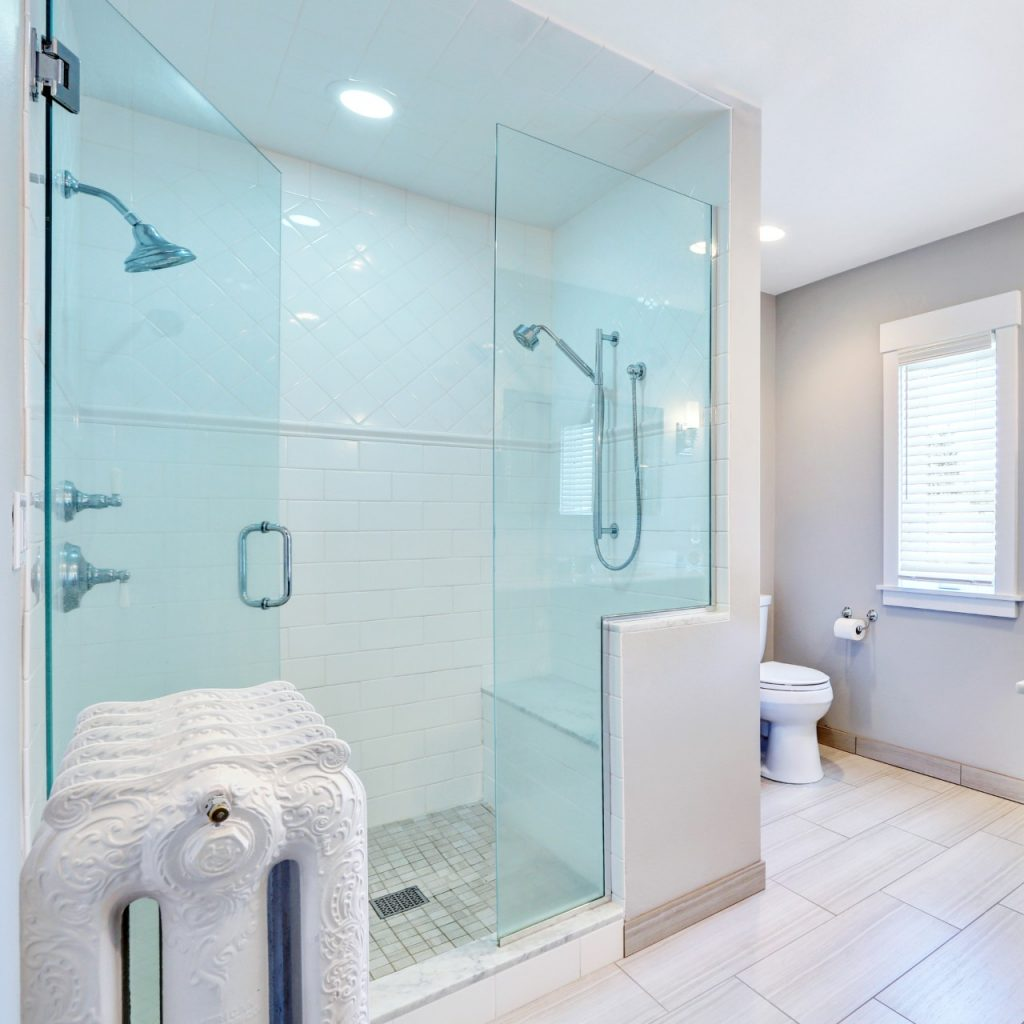 large sitting shower with two shower heads and a frameless glass exterior